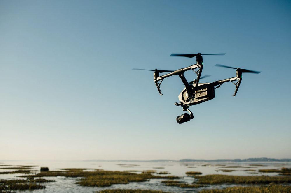 un drone noir en vol au-dessus d'un lac pendant une belle journée ensoleillée