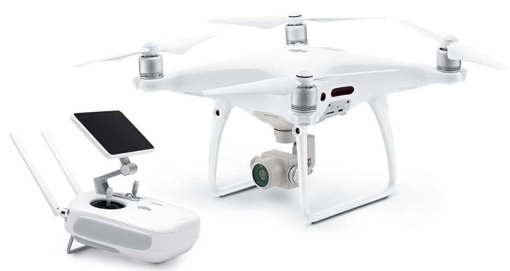 le drone DJI Phantom 4 Pro blanc et sa camera 4k pose a cote de sa telecommande de pilotage