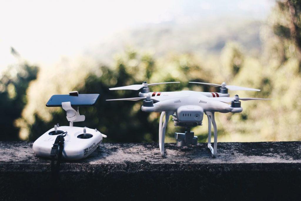 un drone FVP blanc et rouge posé sur un mur avec sa manette de contrôle et un smartphone